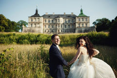 Bride and groom running through the field to castle Royalty Free Stock Images