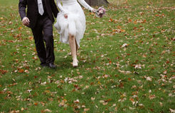 Bride and groom running on grass stock photography