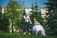 Bride and groom running on the green grass Stock Image