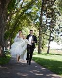 Bride and Groom Running Stock Photography