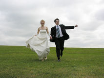 Bride and groom running on meadow stock photos
