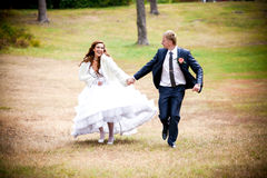 Bride and groom running and park Stock Image