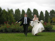 Bride and groom running from trees. Clouds royalty free stock photo