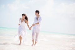 Bride and groom running on a tropical beach Stock Image