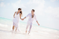 Bride and groom running on a tropical beach Royalty Free Stock Images