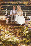 The bride and groom in a rustic style hugging sitting on stone steps at autumn forest, surrounded by wedding decor. Stock Photography
