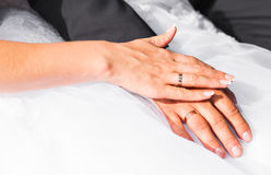 Bride and groom's arms with rings Stock Images