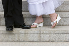 Bride and groom's feet in shoes. A bride and groom stand toe to toe in their wedding shoes. Closeup Royalty Free Stock Photography