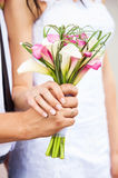Bride and groom's hands with bouquet of callas Stock Images