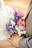 Bride and groom's hands with flowers bouquet Royalty Free Stock Image