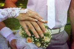 Bride and groom`s hands with golden rings. Putting wedding dress on with the help of second person Royalty Free Stock Photos