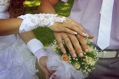 Bride and groom`s hands with golden rings. Putting wedding dress on with the help of second person Stock Photo