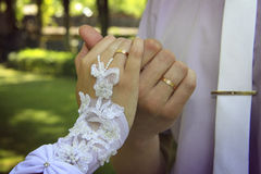 Bride and groom`s hands with golden rings. Putting wedding dress on with the help of second person Stock Image