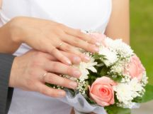 The bride and groom's hands together. On the wediing bouquet Stock Images