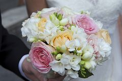 Bride and groom's hands with wedding bouquet Stock Image