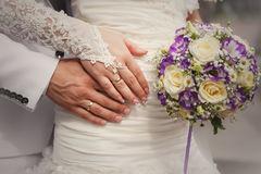 Bride and groom's hands with wedding bouquet and rings Stock Images