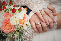 Bride and groom's hands with wedding bouquet and rings Stock Photos