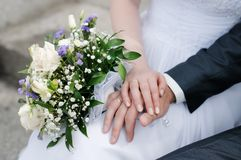 Bride and groom's hands with wedding rings. And bouquet of flowers Stock Image