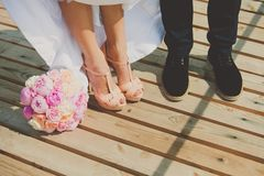Bride and groom's shoes on the brown wooden floor. With bouquet of peonies. Close up of wedding couple legs Stock Photos