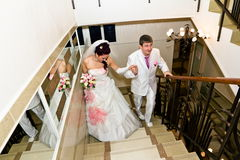 The bride and groom's wedding attire go up the stairs Stock Images