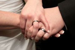 Bride and Groom's Wedding Bands. Bride and Groom holding hands showcasing their wedding bands Stock Image