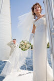 Bride and groom sailing on white yacht Royalty Free Stock Image