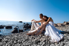 Bride and groom on sea coast Stock Photos