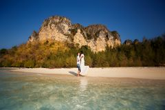 Bride and groom at sea edge against cliffs. Bride and groom barefoot at edge of transparent water against cliffs and tropical trees Stock Photos