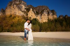 Bride and groom at sea edge against cliffs. Bride and groom barefoot at edge of transparent water against cliffs and tropical trees Stock Image