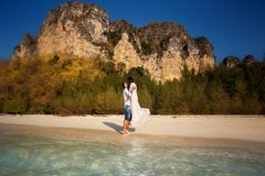 Bride and groom at sea edge against cliffs. Bride and groom barefoot at edge of transparent water against cliffs and tropical trees Stock Images