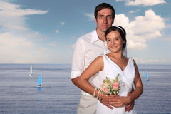 Bride and groom at the sea. Bride and groom with sailing boats in the background Royalty Free Stock Image