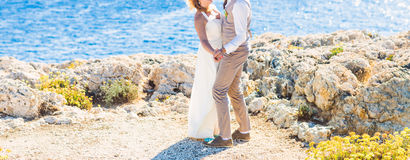 Bride and groom by the sea. On their wedding day Stock Image