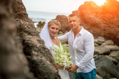 Bride and groom by the sea on their wedding day. Bride and groom by the sea rocky beach on their wedding day. Happy together Stock Image