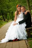 Bride and groom seated in park Royalty Free Stock Image