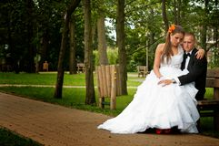 Bride and groom seated in park Stock Photography