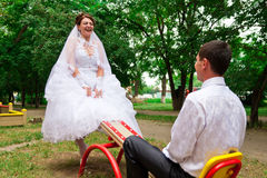 Bride and groom on a seesaw royalty free stock photos