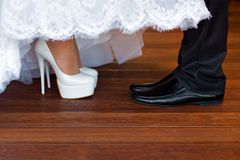 Bride and Groom Shoes. Bride's white wedding shoes and groom's black wedding shoes Royalty Free Stock Photography