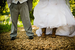 Bride and Groom Shoes and Boots. Bride and groom in tuxedo and wedding dress. Bride wearing boots. Country bride wedding royalty free stock image