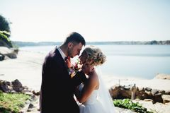 Bride  and groom shooting and walking along the river. Lovers hug, groom tenderly holding his bride`s neck, smiling and they looking into each other`s eyes Stock Image