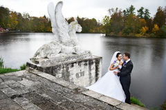 Bride and groom on shores of lake stock photo