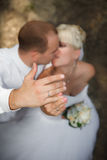 Bride and groom are  show up the hands with wedding rings and kissing Royalty Free Stock Photography
