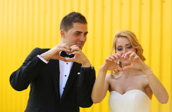 Bride and groom showing love sign with their hands Stock Image