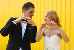 Bride and groom showing love sign with their hands Royalty Free Stock Images