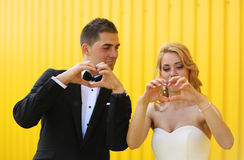 Bride and groom showing love sign with their hands Stock Photos