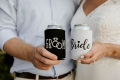 Excited Caucasian Bride & Groom Posing while Showing Off Custom Black and White Drink Beverage Koozies on their Big Wedding Day royalty free stock image