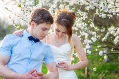 Bride groom shows his biceps on the background of a flowering tree Stock Image