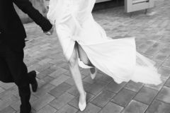 The bride and groom are on the sidewalk, legs close-up. Black and white royalty free stock photo