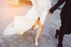 The bride and groom are on the sidewalk, legs close-up. Fluttering dress. The girl covers her legs. Pavement stock image