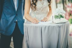 Bride and groom sign documents stock image