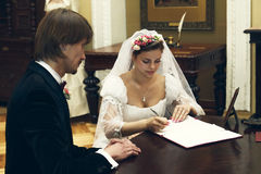 The bride and groom sign the marriage contract Royalty Free Stock Image